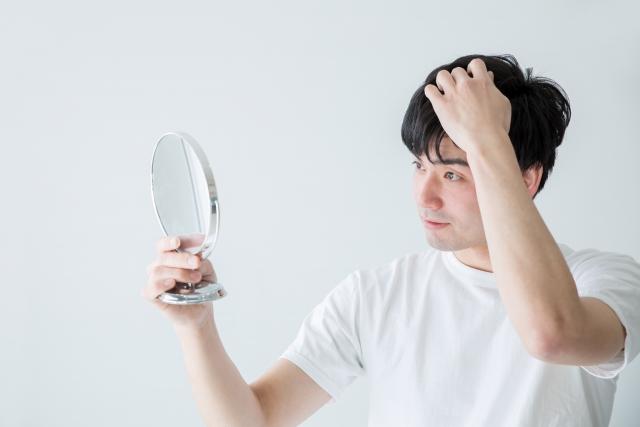 頭髪を気にして鏡を見る男性