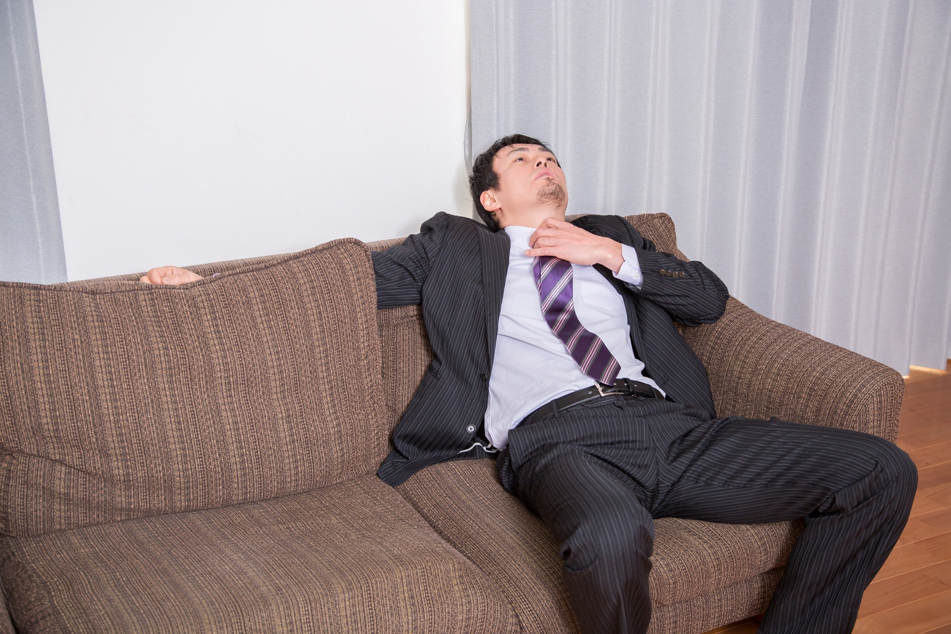ソファでぐったりする男性会社員