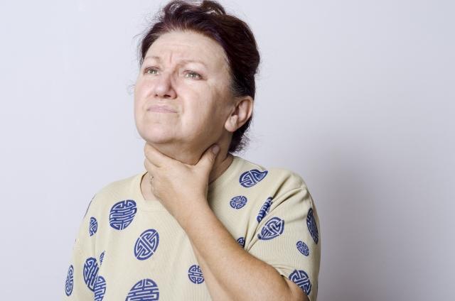 喉に手を当てる高齢女性