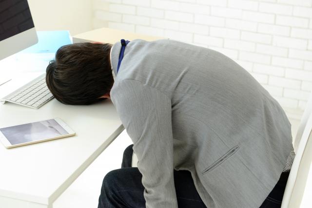 疲れて机に伏せる男性